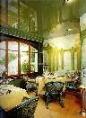 Зеленый глянцевый натяжной потолок в комнате